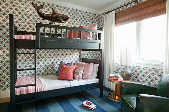 Fun shared boys' bedroom features walls clad in red and green print wallpaper lined with black bunk beds fitted with ladder dressed in white and red stripe bedding alongside whale art.