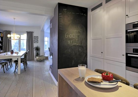 Kjøkkenet er i hvitt og lyst tre, med integrerte hvitevarer. hele ...