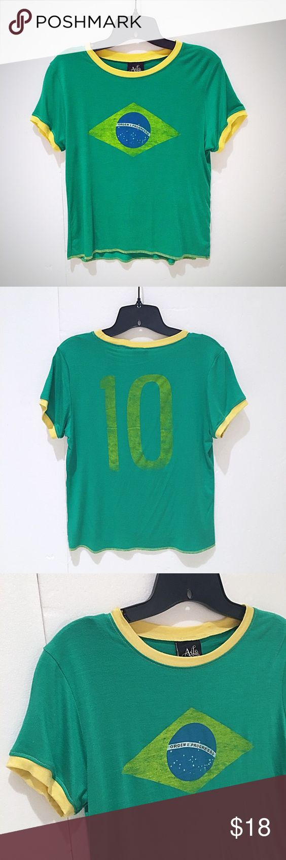 Vintage Green Ringer Tee Made by As-Is. Unique Green Ringer Tee with Brazilian Flag. Intentional faded screen-print design front & back for a vintage look. Yellow accented trim. Contrast surge-stitched hem at bottom. Has a slight cropped fit to it, but depending on size, may hit exactly at upper waist for a size XS or S. 95%Cotton, 5%Spandex, machine wash gentle, lay flat to dry. Very lightweight smooth cotton feel fabric with plenty of stretch, so yes-if your a Med & want it tight, it'll…