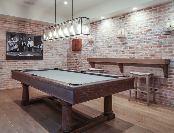 The brick walls on this basement really make it look more rustic and the small wood bar on the side and wood surround on the pool table make it just the right mix. Plus the wood floor improves the whole look.