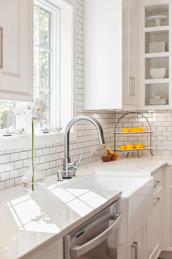 Farmhouse sink with Misty Carrara Caesarstone quartz countertop and subway tile backsplash. New England Design Works:
