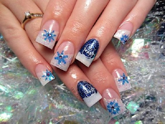 Perfect in white and blue combination. Celebrate a blue Christmas with this nail art design. Use a glitter white polish for the French tips and paint on fun looking designs topping them off with silver beads.