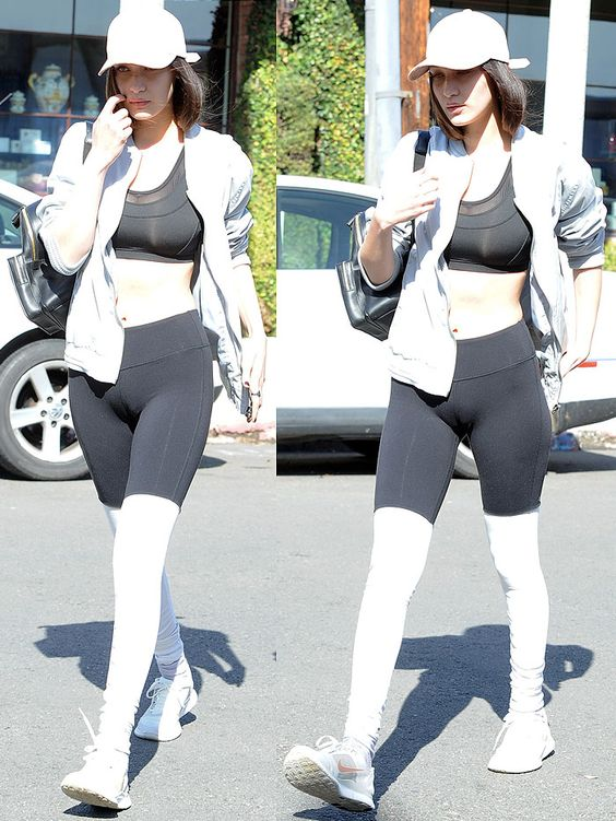 "Bella Hadid dressed in a Vianel leather baseball cap, Solow dotted herringbone sports bra, Alo ""Goddess"" leggings, and Nike sneakers to get coffee and hit up a bookstore"