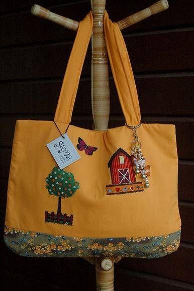 Bolsa confeccionada em tecido de algodão laranja e estampado, com apliques, possui alça forrada com manta, fecho imantado, forro com manta, dois bolsos embutidos na parte interna e chaveiro de borboletas. A alça tem 30 cm. R$49,90
