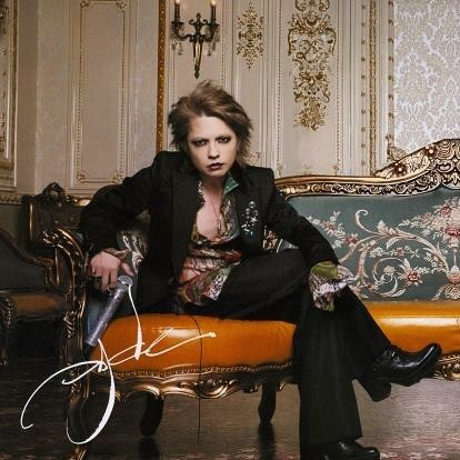 黒いスーツを着たソファーに座っているL'Arc〜en〜Ciel・hydeの画像