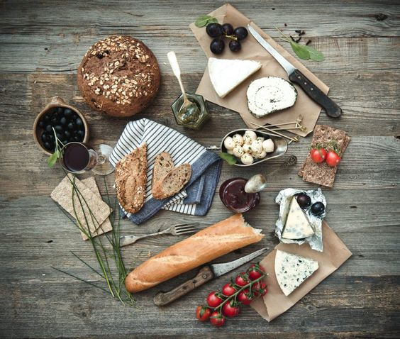 French food on a wooden background. Different types of cheese, wine and other…