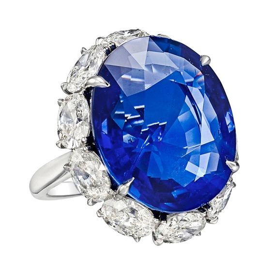 Ceylon sapphire and diamond ring, centering on an oval-shaped sapphire weighing 22.32 carats, with an oval-shaped diamond surround weighing approximately 4.10 total carats, mounted in platinum.
