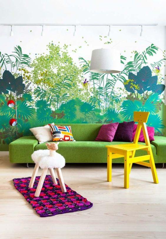 An der Wand dient ein Waldmotiv als Hintergrund für bunte Möbel