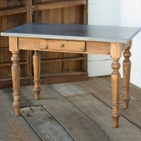 Turned post legs and a jauntily placed center drawer fall under the spell of an aged finish zinc top. Go ahead: dish out dinner, homework, craft projects or birthday cupcakes. This table works. brb...