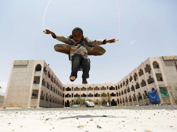 Garoto pula corda em frente a uma escola onde refugiados foram abrigados após conflitos na província de Houthi, ao norte do Iêmen - 05/08/2015