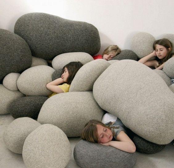 al mohadas de varios tamaños en forma de rocas y cutro niñas acostadas en ellas