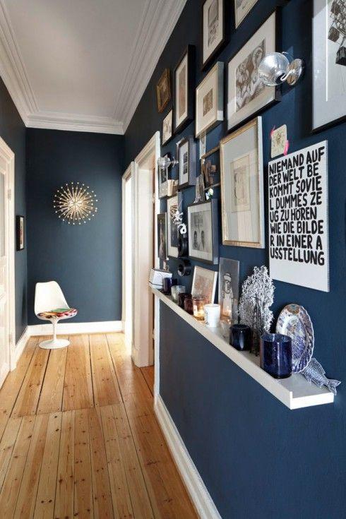 Mur bleu pétrole pour une entée en couloir avec un mur de photos et de citations... L'art d'optimiser l'espace en toute modernité ! Le sol en parquet clair et les appliques en métal apportent une luminosité à la pièce... L'astuce pour agrandir ce couloir étroit : installer une longue et fine étagère blanche tout au long de l'allée de la même couleur que les plinthes, pour faire un rappel et donner une impression de grandeur. #déco #décoration #intérieur #maison #entrée #design #moderne #chic