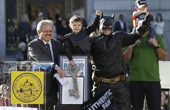 Miles Scott, dressed as Batkid, second from left, raises his arm next to Batman at a rally outside of City Hall with Mayor Ed Lee, left, and...