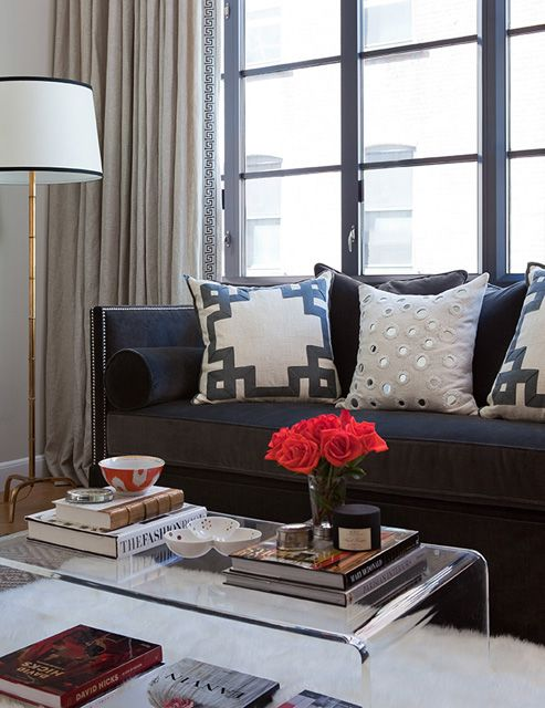 Dark velvet couch, lucite table, flowers bringing a pop of color.