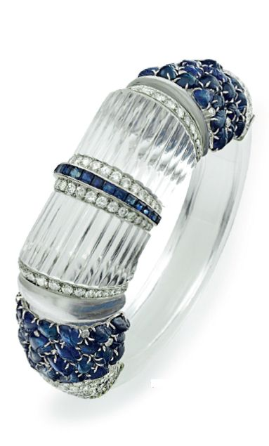 An Art Deco rock crystal, sapphire and diamond bangle, circa 1935. Designed as a hinged bangle, with circular-cut diamonds and carved sapphires, centring upon two reeded rock crystal panels spaced by calibré-cut sapphires and circular-cut diamonds, mounted in platinum. #ArtDeco #bracelet