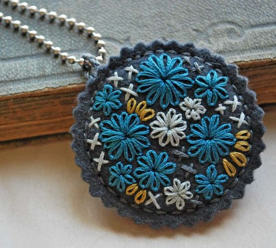 Pewter grey wool felt hand embroidered in turquoise, pale blue and mustard yellow and matching pewter grey thread.    The pendant is 2 inches (5cm) in diameter. It has a piece of chipboard sewn securely inside to keep the circles shape. The pendant lies flat and hangs from a silver toned 24 inch (61cm) ball chain.    Pattern-Her Random Wanderings    Thank you for taking the time to look at my work.