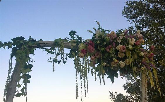 matrimonio. rito simbolico all'aperto. arco di legno slavato con fiori misti di stagione, amaranto ed edera. agosto 2016
