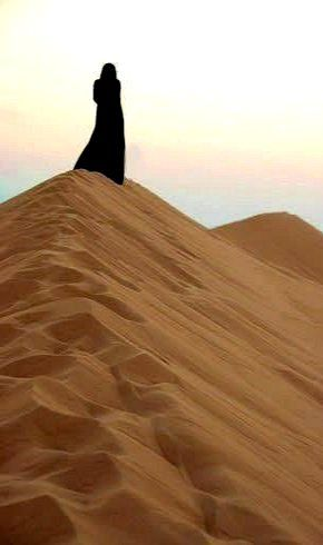A Somali woman on the very top of the dune.