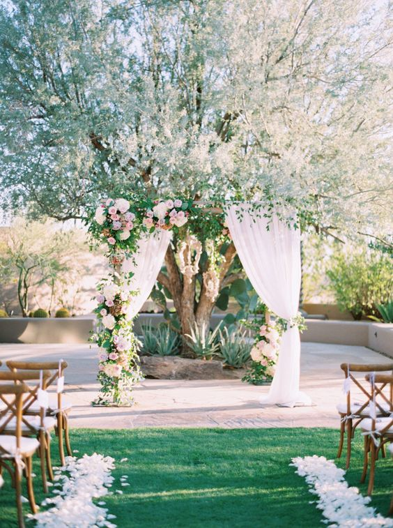 Sunset floral wedding arch: Groom's Attire: Ralph Lauren - http://www.stylemepretty.com/portfolio/ralph-lauren-from-selfridges-london Reception Venue: Four Seasons Resort Scottsdale  - http://www.stylemepretty.com/portfolio/four-seasons-resort-scottsdale- Floral Design: The Flower Studio - http://www.stylemepretty.com/portfolio/the-flower-studio   Read More on SMP: http://www.stylemepretty.com/2017/03/01/prepare-to-fall-head-over-heels-for-the-desert-at-sunset/: