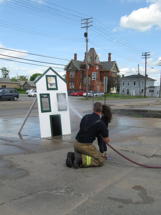 kinder kids practice spraying the hose during fire safety week. Easy to make house! Great idea!