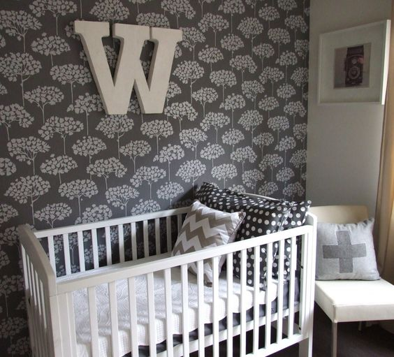 Wallpapered accent wall adds such an impact on this lovely gray nursery!