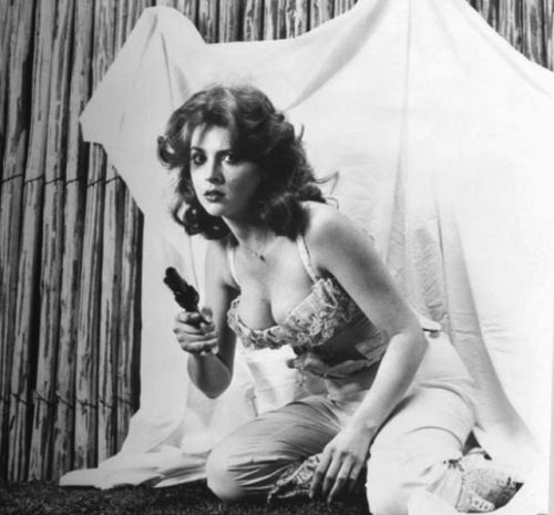 "Tina Louise pulls a revolver. Later, she'll star in the silly sitcom ""Gillian's Island."" Maybe, if she had kept the gun and used it on the Gilligan set, the TV show wouldn't have been so silly!"