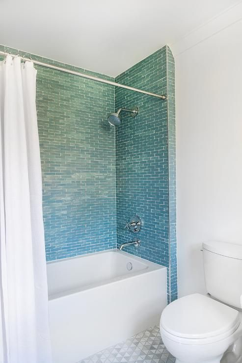 A Chrome Shower Kit Is Mounted To Blue Mini Wall Tiles Over A White Drop In Bathtub Covered With A White Shower Tile White Shower Curtain Blue Tile Backsplash