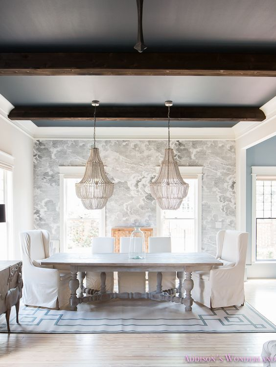 Our dining room reveal... A traditional dining room features cloud wallpaper, double beaded chandeliers, parsons chairs and a beautiful wooden cabinet.