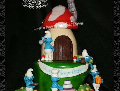 "Smurfs themed 3-D cake for an Icing Smiles recipient.  Bottom tier carved from 10"" rounds (3-layers). House carved from 6"" & 4"" rounds. All figures and decoration details are made from MMF, RKT & modeling chocolate."