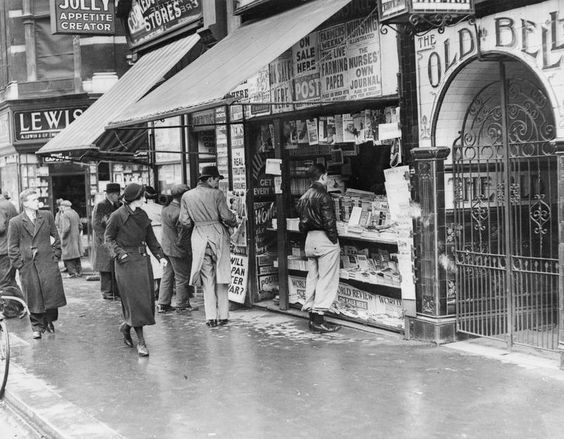 London, Spring 1941: Men and women stop to look at the headlines as they pass a newsstand on London's Fleet Street. The Old Bell tavern is also visible on the right of the photograph.