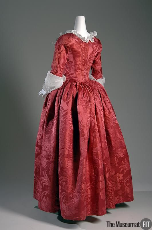 ca. 1775 Robe a l'anglaise in red silk damask. The silhouette of this dress is enhanced by the fabric's rich color and vibrant pattern - a sumptuous display of fruit and flowers. The fabric was designed by Anna Maria Garthwaite, an English textile designer and the only woman known to have worked in Spitalfields, a silk-weaving center in London. | The Museum at FIT. Object Number: 2008.4.1