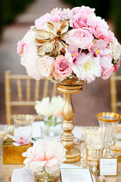 A gilded flower adds glamour to a centerpiece of pink and white peonies and roses.: