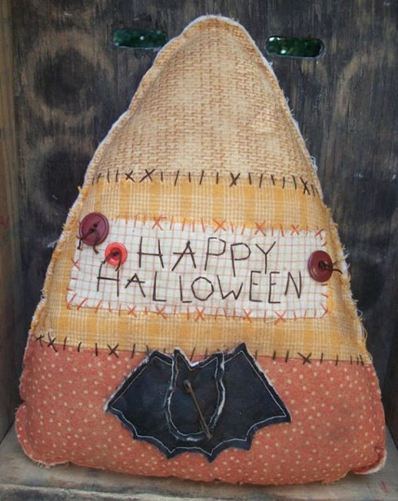 This Candy Corn greeter can be hung for display or used like a cupboard tuck. Made from pieced fabrics in orange and yellow, it features a patched-on bat, hand stitching and buttons. Measuring approximately 12 tall and 10 wide, candy corn is lightly stuffed, grunged and ready to ship. Made from my own design and pattern for The Wooded Lake 2011/2016.   Free shipping to US! Please contact me for cost/availabilty for all other locations.