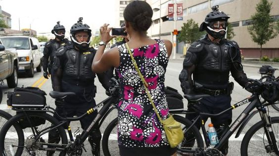 A demonstrator takes a picture of the police bicycle line.