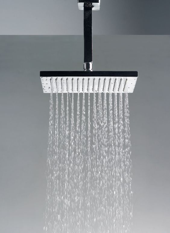 A ceiling mounted rain head in the shower makes use of the ceiling ...