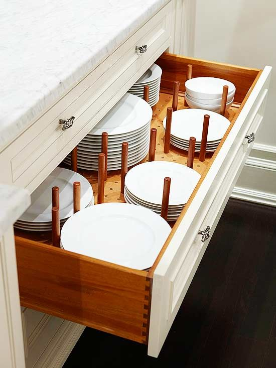 Enter the utilitarian pegboard. Tall pegs, inserted into the pegboard that lines the bottom of the drawer, keep dishes in place to minimize potential chipping and breaking. Plus, the pegs can be reconfigured if you want to change arrangements or get new dishes that are a different size.