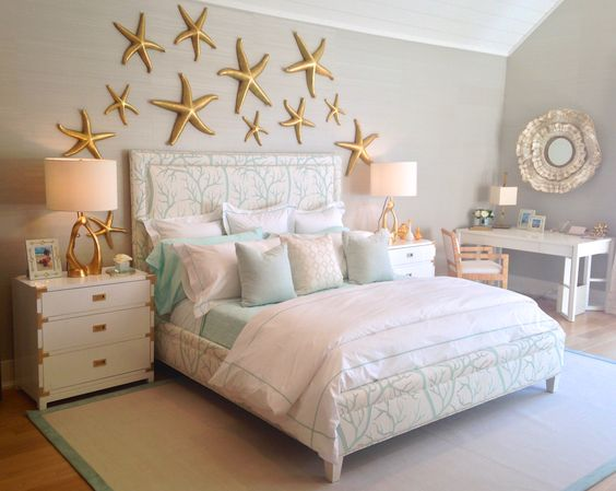 under the sea themed bedroom with a coral print upholstered bed & gold starfish on the wall