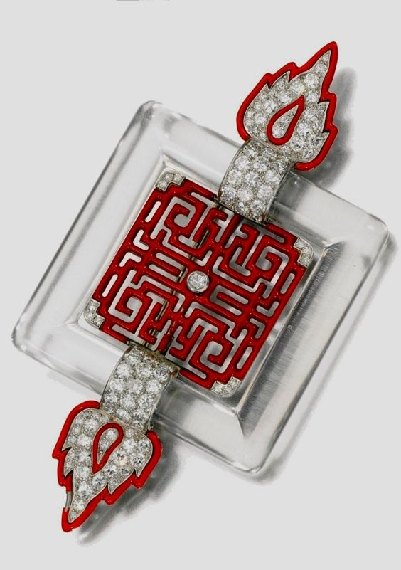 An Art Deco enamel, rock crystal and diamond brooch, Cartier, 1920s. Set at the centre with an openwork red enamel plaque of Chinese inspiration, within a frame of rock crystal set between a pair of red enamel flame motifs set with circular-cut diamonds, signed Cartier and indistinctly numbered. #Cartier #ArtDeco #brooch