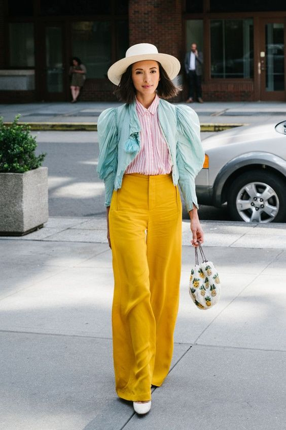 Street style at New York Fashion Week spring 2018. Love the pineapple handbag. Sleeves like cotton candy sky blue pink striped shirt and bright yellow wide legged pants