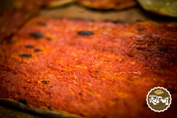 Pizza Rossa, Red Pizza.  It has the same dough of the white one, but it is spiced with raw tomatoes, oregano and biologic wheat salt. Crispy and very thin, it is very good both warm and cold.