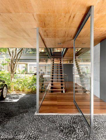 Com estrutura de alumínio, a porta pivotante (Dinafex, execução da Jmar) define a entrada. Ela também marca a transição entre o mosaico português (Marmoraria Butantã) da garagem e as réguas de cumaru (Pau-Pau), no hall e no piso superior. Projeto do arquiteto Fernando Viegas.