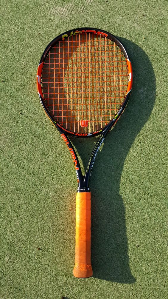 Photo of a Wilson Burn 100S tennis racquet with orange Volkl Cyclone strings.