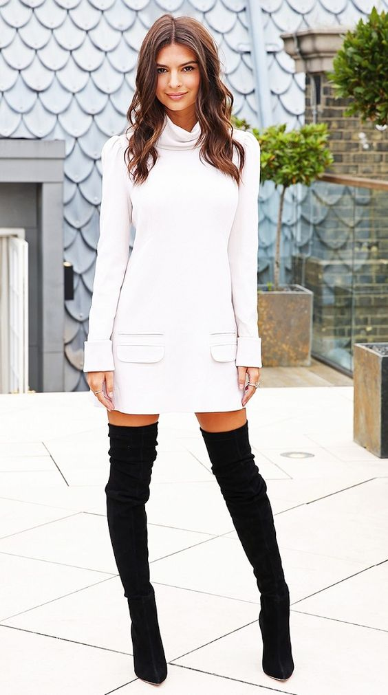 Emily Ratajkowski wears a white turtleneck shift dress by Zimmermann and Brian Atwood thigh-high boots: