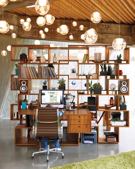 """Bishop is an avid record collector—Rolling Stones albums are a sought-after favorite—and he keeps his vinyl in the shelving unit """"1.1,"""" a reproduction of Arbel's first completed work. The kids can often be found playing video games at the desk in the great room."""
