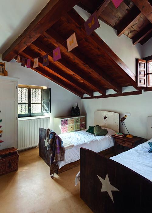 """Buardilla para dormitorio infantil, ideal para que tengan """"su espacio"""". Tonalidades en blanco y colores claros hacen destacar la esencia de la madera, en los techos y en el mobiliario. Original diseño de las camas, piecero y cabecero con motivo de estrella"""