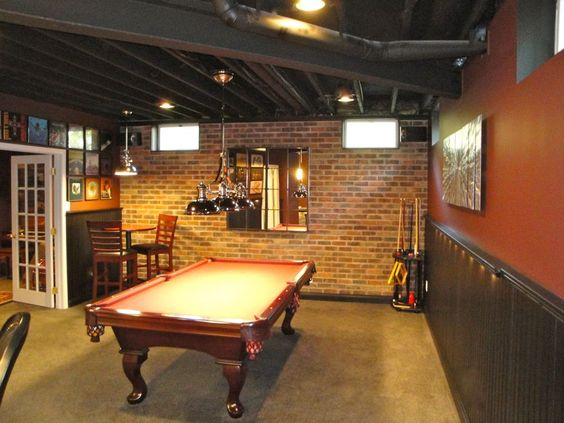 This is a little more simplistic style for your rustic basement ideas because it just has a simple wainscoting and brick wall alongside older style games. It's definitely something you can save a little on but still enjoy.