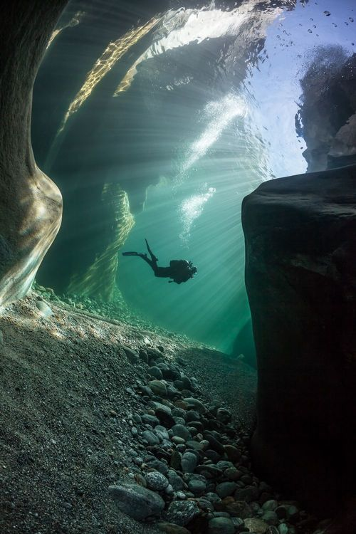 A diver in the crystal clear water of the Verzasca River in Ticino Switzerland. You can see the surface from the bottom of the river. Photo credit: Marc Henauer