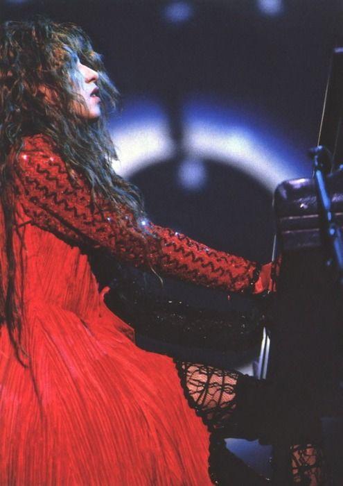 赤いロングコートを着てピアノを弾いているXJAPAN・YOSHIKIの画像