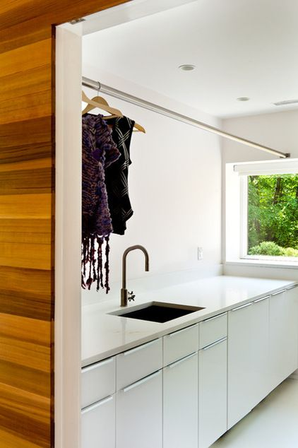modern laundry room by Jeff Jordan Architects LLC | The simple palette of cedar walls and white epoxy floors continues into the utility areas as white walls and cabinets. The contrast with the wood makes these spaces appear even brighter.