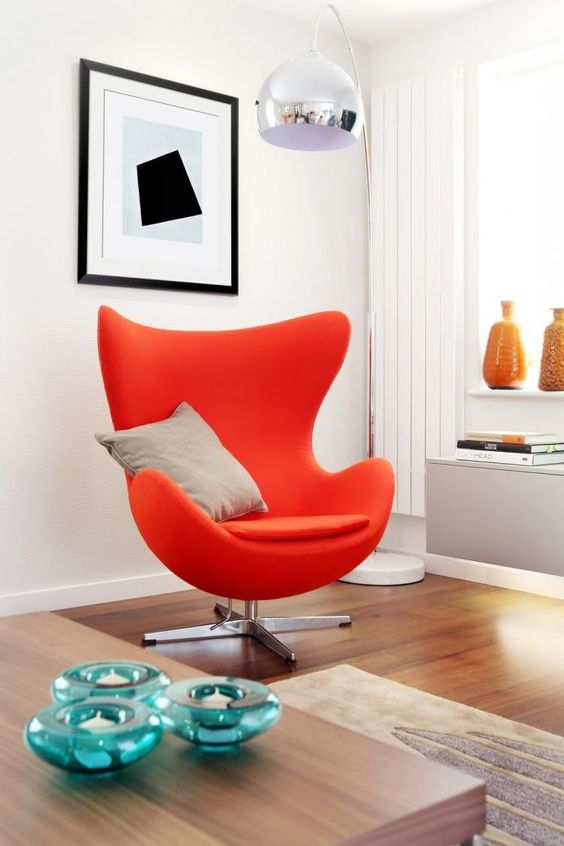 lampadaire arc métallique et fauteuil Oeuf Jacobsen en rouge orangé dans le salon blanc: